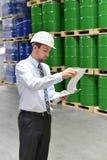 后勤公司工作的经理在有化学制品的一个仓库里 图库摄影
