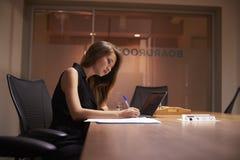 后单独工作在办公室的年轻亚裔女实业家 图库摄影