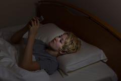 后发短信在晚上的青少年的女孩,当在床上时 免版税库存图片