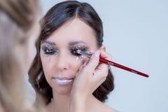 后台场面:做魅力式样构成的专业化妆师在工作 秀丽有美丽的模型妇女做 免版税库存图片