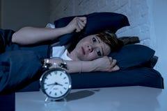 后在床上的年轻美丽的妇女在遭受失眠的晚上设法睡觉 免版税图库摄影