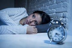 后在床上的西班牙妇女在家卧室在设法的晚上睡觉遭受的失眠 库存图片