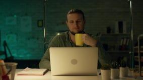 后在私人办公室巩固的商人工作的晚上在膝上型计算机 他通过赢得国际性地成功大 影视素材