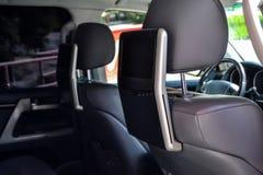 后坐的乘客的娱乐系统有在前座的后面登上的两台显示器的一辆汽车的看着电视的, 免版税库存图片
