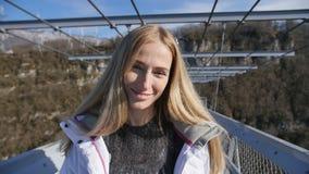 今后妇女步行通过在峡谷的高桥梁在照相机前面 影视素材