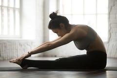 今后实践普拉提脊椎舒展锻炼的年轻运动的妇女 免版税库存图片