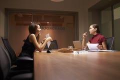 后工作在办公室的两个女性企业同事 图库摄影