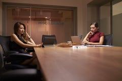 后工作在办公室的两名女实业家使用计算机 免版税库存图片