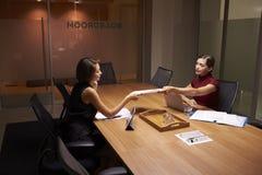 后工作在办公室的两名女实业家通过文件 库存照片