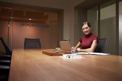 后工作在办公室的年轻女实业家微笑对照相机 免版税库存照片