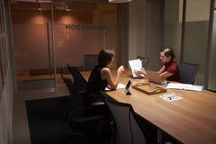 后工作在办公室神色的两名女实业家在文件 免版税图库摄影