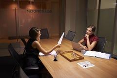 后工作在办公室神色的两名女实业家在文件 免版税库存图片