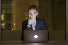 后工作在她的膝上型计算机的,夜光办公室的女实业家 免版税库存照片