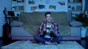 后打电子游戏的十几岁的男孩在夜瘾,缺乏家长监督 免版税库存照片