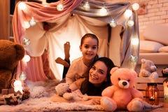 后拥抱的母亲和女儿在枕头房子里在晚上在家 库存照片