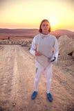 今后看击剑者人佩带的白色操刀的服装拿着剑和 库存图片