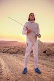 今后看击剑者人佩带的白色操刀的服装拿着剑和 免版税图库摄影