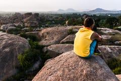 今后看年轻的人坐在山边缘和 库存照片