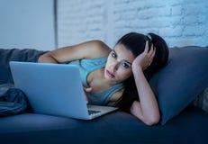 后研究和聊天她的膝上型计算机的上瘾的美丽的妇女在看起来的晚上用尽 图库摄影