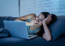 后研究和聊天她的膝上型计算机的上瘾的美丽的妇女在看起来的晚上用尽 免版税图库摄影