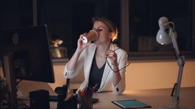 后研究计算机在晚上然后离开玻璃和摩擦疲乏的眼睛的俏丽的年轻女人秘书和 股票录像