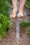 以后赤足走通过水坑的一个少妇的脚 库存图片
