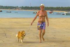 今后走与他的狗的老人在海滩 免版税库存图片