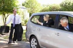 后跑的商人遇见合并旅途的同事汽车入工作 免版税库存图片