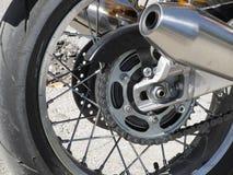 后轮和一辆经典摩托车的被镀铬的排气管 侧视图 免版税库存照片
