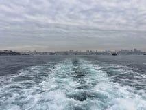 后边波浪在海的一艘船 免版税库存照片