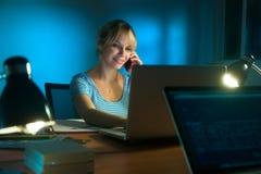 后运转在晚上的妇女室内设计师手机 免版税库存照片