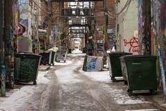 后退在多雪的都市胡同的被打翻的大型垃圾桶 库存照片