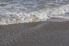 后退在岸的泡沫似的海浪 库存照片