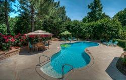后院游泳池在一个晴天 库存图片