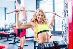 后面体育训练的女孩在健身健身房 库存照片