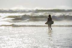 后面光攀爬年轻愉快的亚裔妇女画象放松看在日落热带海滩的狂放的海波浪 免版税库存照片