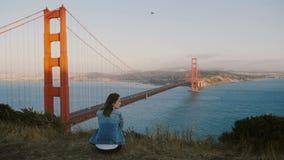 后面单独坐在史诗风景的看法年轻地方妇女思考在美好的日落视图在金门大桥美国 股票视频