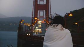 后面单独站立在黑暗的金门大桥交通视图的看法年轻地方妇女在温暖的白色毯子盖的美国 股票录像