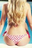 后面和屁股年轻白肤金发的妇女在泳装坐的游泳池边 免版税库存图片