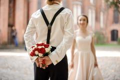 后面图af拿着他的新娘的新郎婚姻的花束 免版税库存照片