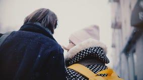 后面在偶然温暖的衣裳的看法愉快的轻松的年轻浪漫夫妇在一个多雪的冷的冬日一起走并且亲吻 影视素材