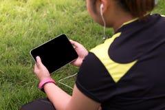 后面坐草地和演奏片剂的看法少妇 免版税库存图片