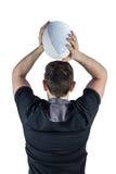 后面投掷球的被转动的橄榄球球员 免版税图库摄影