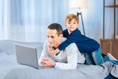 后面拥抱他的父亲的爱恋的儿子研究膝上型计算机 图库摄影