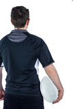 后面拿着球的被转动的橄榄球球员 免版税图库摄影