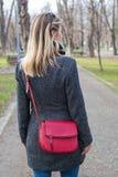 后面有室外红色的袋子的看法白肤金发的妇女 免版税图库摄影