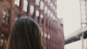 后面有照相机的看法专业女性摄影师在Dumbo区,纽约4K为布鲁克林大桥照相 股票录像