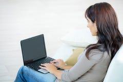 后面有膝上型计算机的看法美丽的被集中的妇女在沙发 免版税库存图片