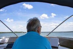 后面特写镜头观点的驾驶在湖的太阳镜的灰发的人一条小船有房子和海岸线的天际的在蓝色c下 免版税库存照片