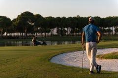 从后面的高尔夫球运动员在看对在距离的孔的路线 图库摄影